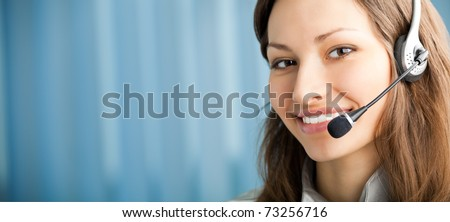 Portrait of happy support phone operator in headset at workplace. To provide maximum quality, I have made this image by combination of two photos. You can use left part for slogan, big text or banner. - stock photo