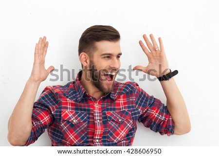 Portrait of happy surprised handsome young man in casual wear sitting against white wall. - stock photo