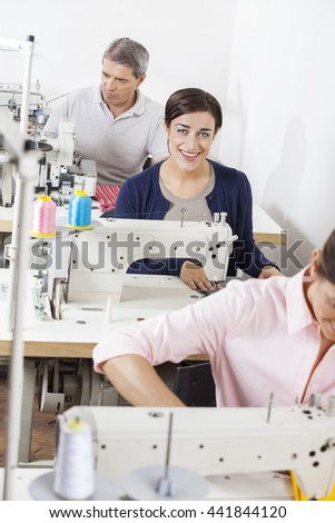 Portrait Of Happy Tailor With Colleagues Working In Factory - stock photo