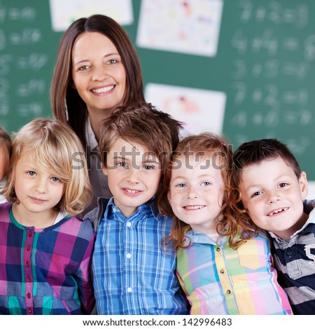 Portrait of happy teacher in classroom with his little happy students in the classroom
