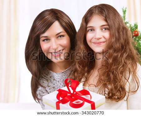 Portrait of happy teen girl with her beautiful young mother celebrating winter holidays at home, enjoying Christmas present - stock photo