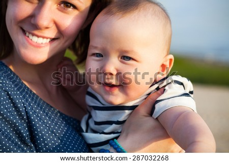 Portrait of happy teen sister and little baby brother on the beach