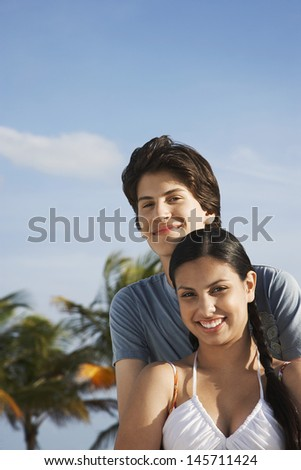 Portrait of happy teenage couple on tropical beach - stock photo