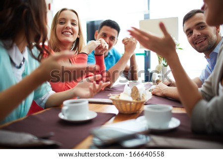 Portrait of happy teenage friends sitting and chatting in cafe - stock photo