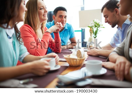 Portrait of happy teenage friends sitting in cafe - stock photo