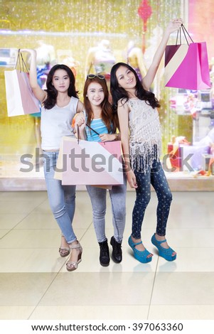 Portrait of happy teenage girls standing in the mall while holding shopping bags