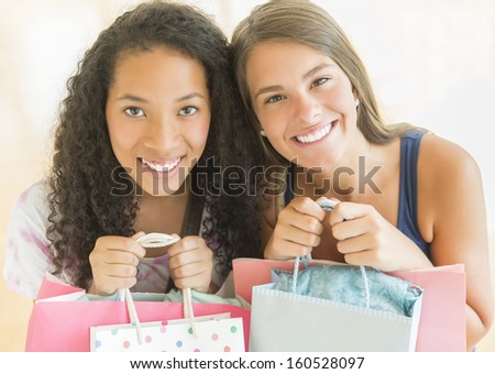 Portrait of happy teenage girls with shopping bags
