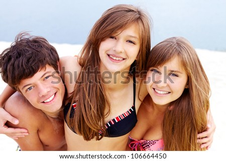 Portrait of happy teenage guy and two pretty girls