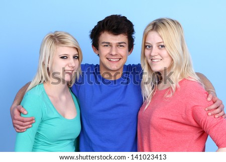 Portrait Of Happy Three Friends On Blue Background