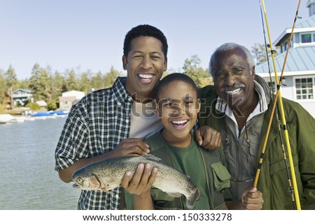 Portrait of happy three generation family with fishing rod and fish at lake - stock photo