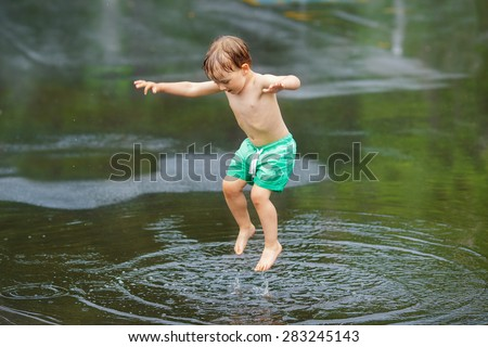 Portrait of happy toddler boy jumping in puddles during the rain thunderstorm on a bright summer day outside, sports recreation leisure concept, childhood and freedom