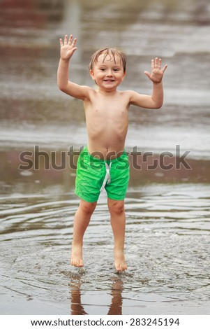 Portrait of happy toddler boy jumping in puddles during the rain thunderstorm on a bright summer day outside, sports recreation leisure concept, childhood and freedom - stock photo