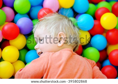Portrait of happy toddler boy playing with colorful balls in ball pit - stock photo