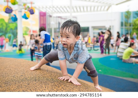 Portrait of happy toddler boy playing with water in puddles during rain thunderstorm on bright summer day outside, recreation leisure concept, childhood freedom