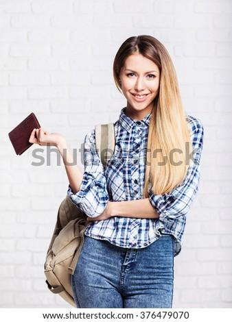 Portrait of happy tourist woman holding passport on holiday - stock photo