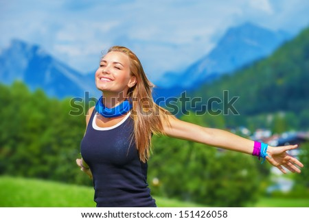 Portrait of happy traveler girl with raised up hands enjoying sunny day, mountains landscape, travel to Europe, happiness emotion, summer holiday concept - stock photo