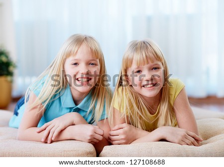 Portrait of happy twins looking at camera at home - stock photo