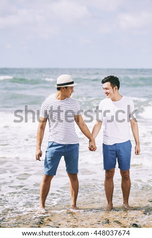 Portrait of happy Vietnamese gay couple at the beach
