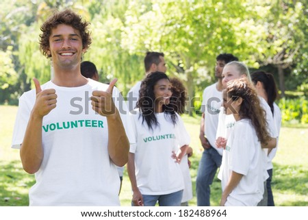 Portrait of happy volunteer gesturing thumbs up with friends disucssing in background - stock photo