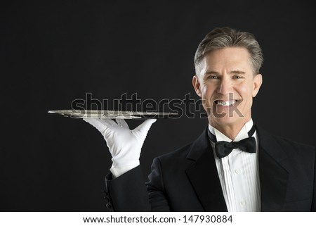 Portrait of happy waiter wearing tuxedo carrying serving tray against black background