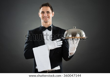 Portrait of happy waiter with tray and towel standing against gray background - stock photo