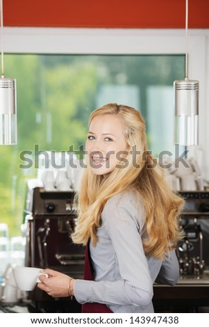 Portrait of happy waitress holding coffee cup against machine in cafe