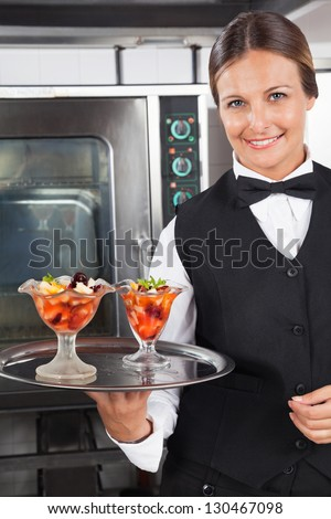 Portrait of happy waitress holding dessert tray in industrial kitchen - stock photo