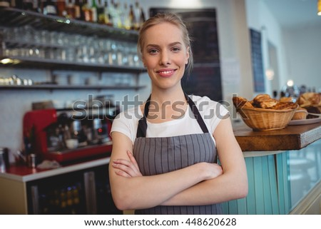 Portrait of happy waitress standing with arms crossed at cafe