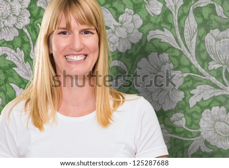 Portrait Of Happy Woman against a vintage wall - stock photo