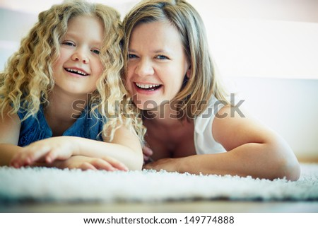 Portrait of happy woman and her daughter looking at camera with laugh