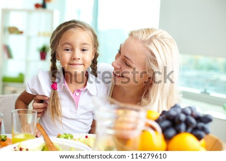 Portrait of happy woman and her daughter sitting at festive table