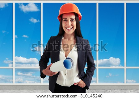 portrait of happy woman architect in orange hardhat holding plan and looking at camera over big windows - stock photo