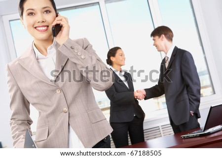 Portrait of happy woman calling on the phone on the background of business people?s handshake