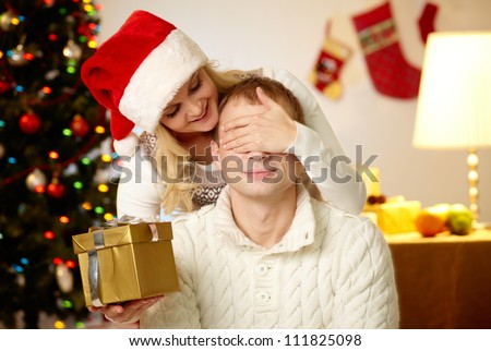 Portrait of happy woman closing male�¢??s eyes by her hands while holding giftbox in front of him - stock photo
