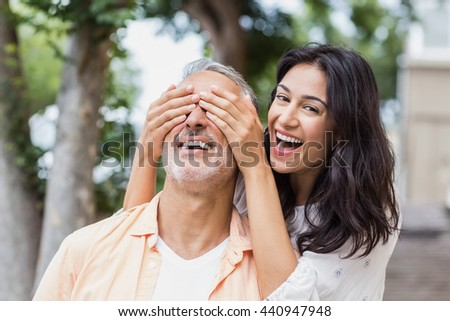 Portrait of happy woman covering mans eyes in city