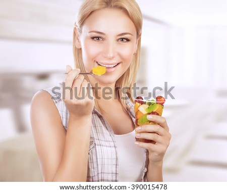 Portrait of happy woman eating tasty fruit salad at home, healthy nutrition, dieting snack, enjoying sweet organic food - stock photo