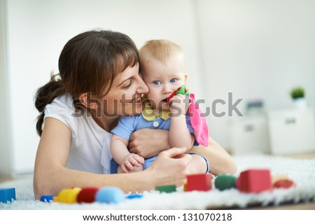 Portrait of happy woman embracing her small son during play - stock photo