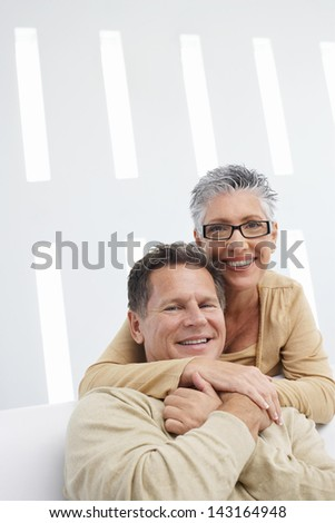 Portrait of happy woman embracing man at home