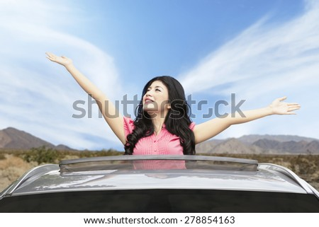 Portrait of happy woman enjoying freedom on the sunroof of new car