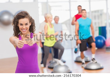 Portrait of happy woman gesturing thumbs up with people exercising in background at gym - stock photo