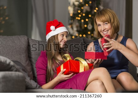 Portrait of happy woman giving Christmas present to daughter at home - stock photo