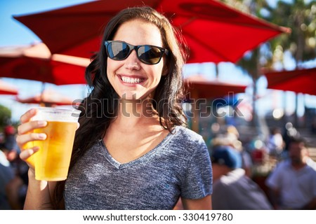 portrait of happy woman holding cup of beer outside on sunny day shot with selective focus - stock photo