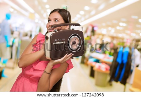 Portrait Of Happy Woman Holding Radio at a mall - stock photo