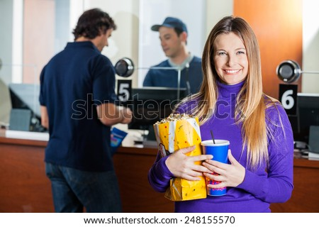 Portrait of happy woman holding snacks while man buying tickets from male seller at box office counter
