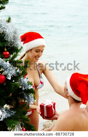 Portrait of happy woman in Santa cap giving giftbox to her husband near xmas firtree on the beach