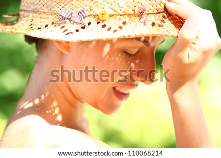 Portrait of happy woman in straw hat on the beach - stock photo