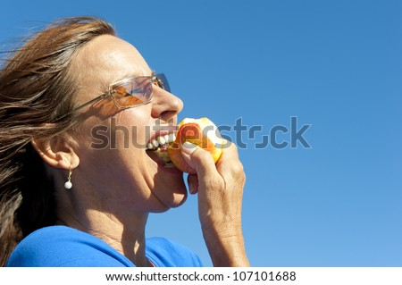 Portrait of happy woman keeping healthy and fit by eating fresh fruits, biting in apple, isolated with blue sky as background and copy space. - stock photo