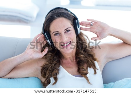 Portrait of happy woman listening to music on sofa at home