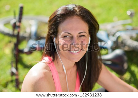 Portrait Of Happy Woman Listening To Music, Outdoors - stock photo