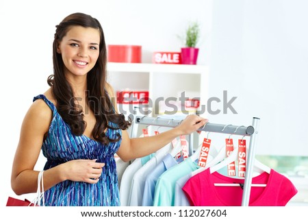Portrait of happy woman looking at camera in clothing department